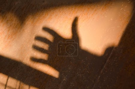 Shadow of a hand on steel