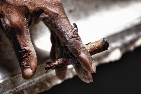 Hand keeping smoldering cigar