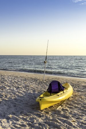 Fishing pole and canoe on the beach