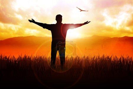 Photo pour Illustration en silhouette d'un homme debout sur un champ d'herbe les bras ouverts face au soleil - image libre de droit