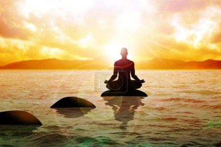 Foto de Silueta de una figura de hombre meditando sobre aguas tranquilas durante el amanecer - Imagen libre de derechos