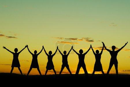 Photo pour Heureuses femmes célébrant au coucher du soleil ou au lever du soleil debout avec les bras levés au-dessus de leurs têtes - image libre de droit