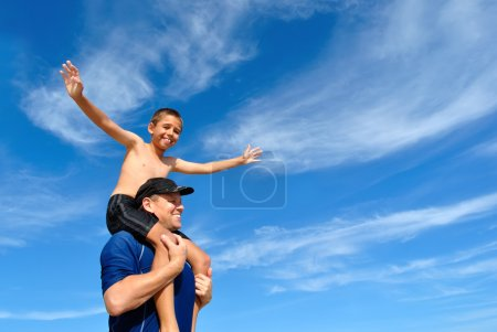 Son balancing on dad's shoulders