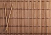Two chopsticks on sushi background