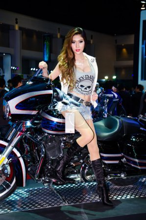 Photo for BANGKOK - MARCH 25: Unidentified model with Harley-davidson FLSTC Heritage Softail Classic motorbike on display at The 35th Bangkok International Motor Show on March 25, 2014 in Bangkok, Thailand. - Royalty Free Image