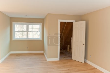 Photo for New home construction interior room with unfinished wood floors and twin closets. The electrical and hvac connections also are partially unfinished. - Royalty Free Image
