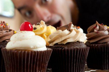 Man Looks At Cupcakes