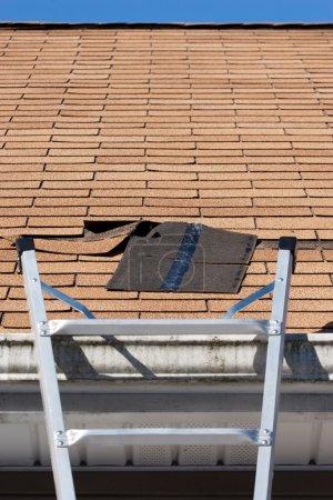 Photo pour Une échelle mises en place pour réparer les bardeaux de toit endommagé. une section a été arrachée après une tempête avec des vents violents causant un risque de fuite. - image libre de droit