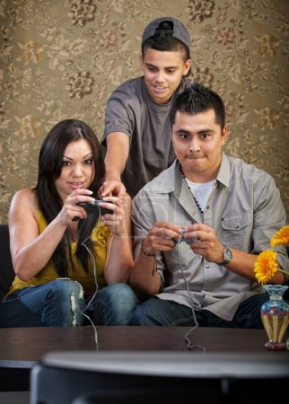 Photo for Teenager shows parents how to use video game controllers - Royalty Free Image