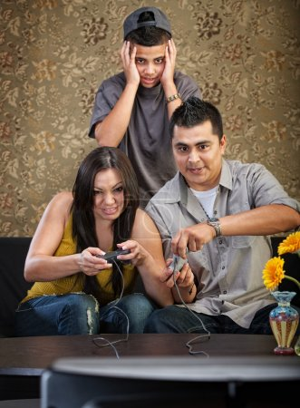 Photo for Embarrassed Hispanic teenager behind parents playing video games - Royalty Free Image