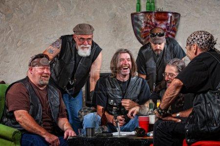 Photo pour Six membres de gangs de motards mâle riant avec armes sur la table - image libre de droit