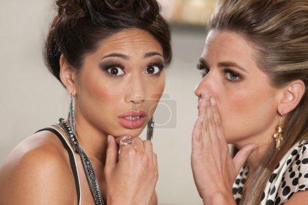 Photo pour Jeune femme soucieuse d'écouter quelqu'un chuchoter des secrets - image libre de droit