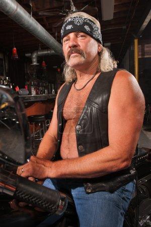 Photo pour Homme âgé du milieu difficile sur moto en bar - image libre de droit