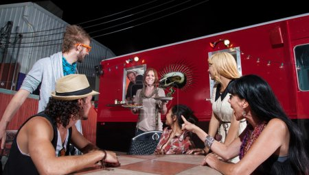 Photo for Cheerful waitress bringing orders to at pizza truck - Royalty Free Image