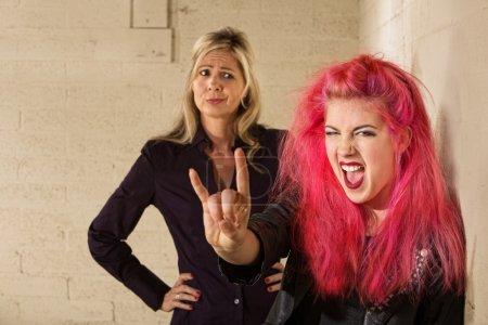 Photo pour Adolescent en cheveux roses avec une mère désapprobatrice en arrière-plan - image libre de droit