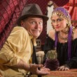 Fortune teller in head scarf with skeptical customer and crystal ball