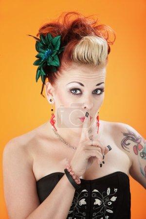 Photo pour Une femme flamboyante, sexy avec son doigt à ses lèvres - image libre de droit