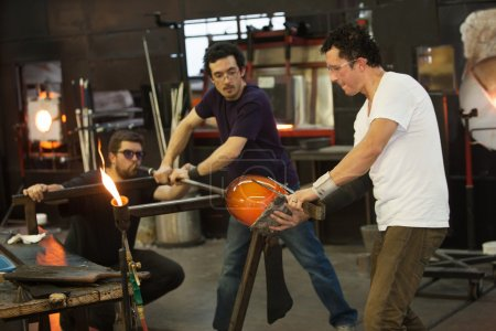 Photo for Three students working with hot glass and blowpipe - Royalty Free Image