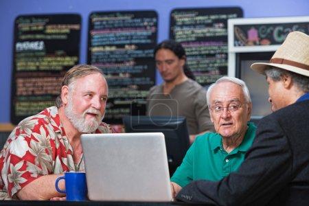 Photo pour Groupe diversifié d'hommes mûrs dans le café avec ordinateur portable - image libre de droit