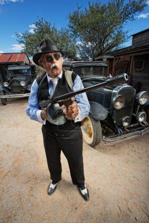 Photo pour Gangster mâle avec lunettes de soleil, de cigare et de mitrailleuse à l'extérieur - image libre de droit