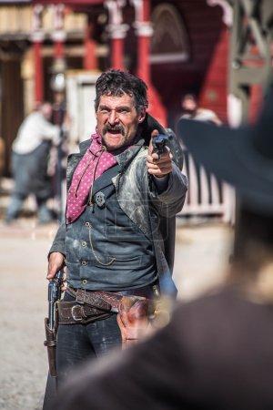 Photo pour Shérif points pistolet à hors-la-loi en ville - image libre de droit