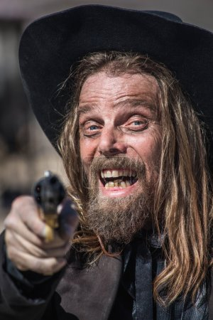 Photo pour Cow-Boy rit lorsqu'il pointe pistolet à vous - image libre de droit