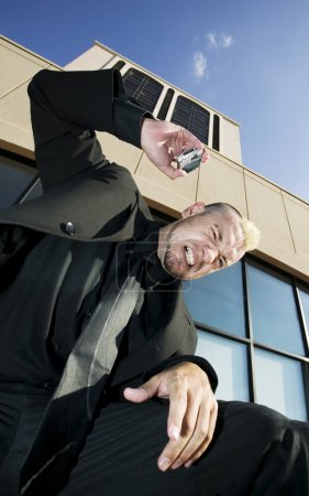 Photo pour Homme d'affaires avec une coupe de cheveux punk montre frustration et colère en ce qui concerne son téléphone portable . - image libre de droit