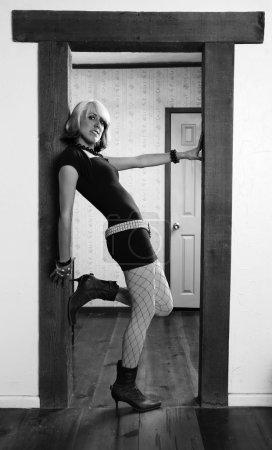 Photo pour Femme en vêtements colorés, appuyé contre un jambage de la porte - image libre de droit
