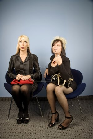 Nervous businesswoman seated next to a bold woman...