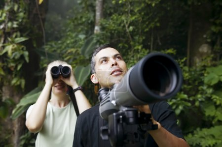 Photo for Pretty Woman with Binoculars and Man with Telescope in Rain Forest Jungle - Royalty Free Image