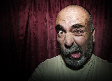 Photo pour Gros plan d'un homme devant des rideaux rouges faisant un drôle de visage - image libre de droit