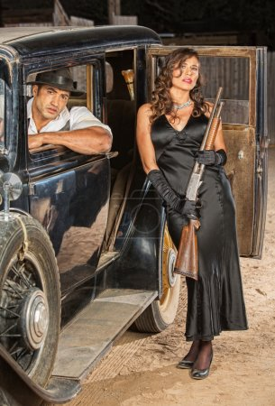 Male and female retro gangsters with shotgun in ca...