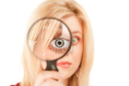 Photo pour Jolie jeune femme blonde regardant à travers le verre grossissant - image libre de droit