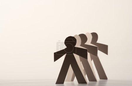 Photo pour Ligne de poupées en papier découpé jetant une ombre - image libre de droit