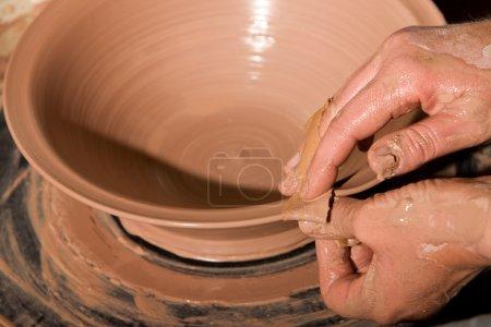 Photo pour Gros plan sur les mains du potier façonner l'argile sur roue - image libre de droit