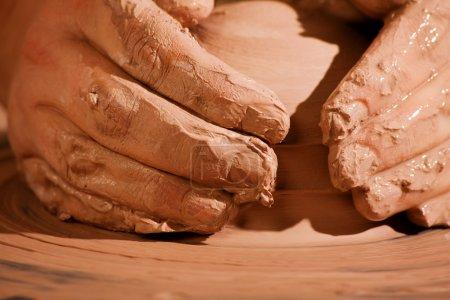 Photo pour Mains formant de l'argile humide sur la roue de poterie - image libre de droit