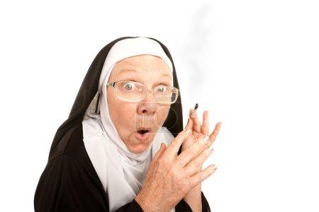 Funny nun suprirsed holding a lit cigarette...