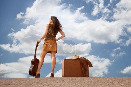Photo pour Jolie femme brune avec valise et guitare - image libre de droit