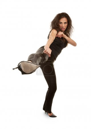Photo for Tough woman in high heels kicking at camera - Royalty Free Image