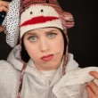 Sick young woman with thermometer and monkey cap...