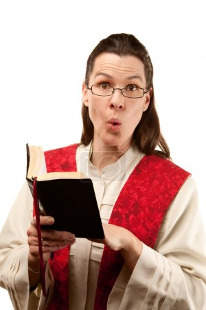 Photo for Pretty female pastor finding something shocking in the Bible - Royalty Free Image
