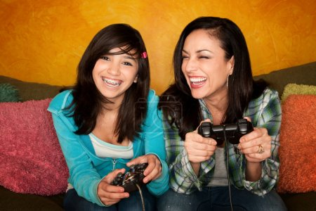 Photo for Attractive Hispanic Woman and Girl Playing a Video Game with Handheld Controllers - Royalty Free Image