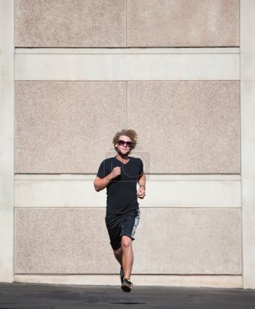Curly haired man runs for exercise.