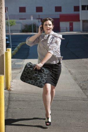 Working woman runs down street.