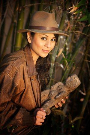 Photo pour Jolie aventurière avec relique volée dans une épaisse forêt de bambous verts - image libre de droit
