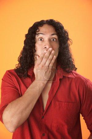 Photo pour Homme hispanique bien bâti exprime son choc avec la main sur la bouche - image libre de droit
