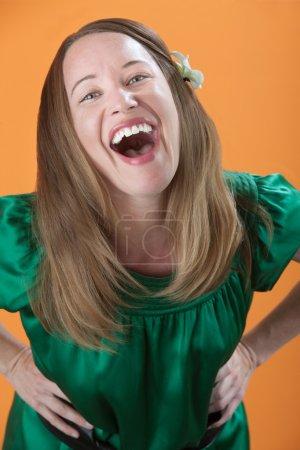Photo pour Belle femme caucasienne riant fort sur un fond orange - image libre de droit