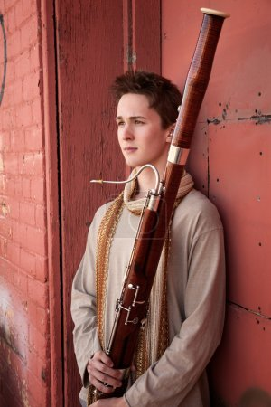 Photo for Young Caucasian man outside holds a bassoon - Royalty Free Image