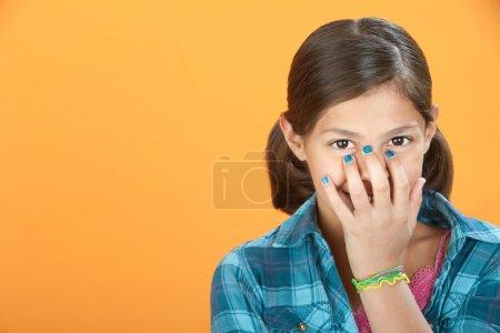 Photo pour Petite fille hispanique couvre un sourire avec sa main - image libre de droit