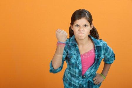 Photo pour Brave en colère petit latino gosse sur un fond orange - image libre de droit